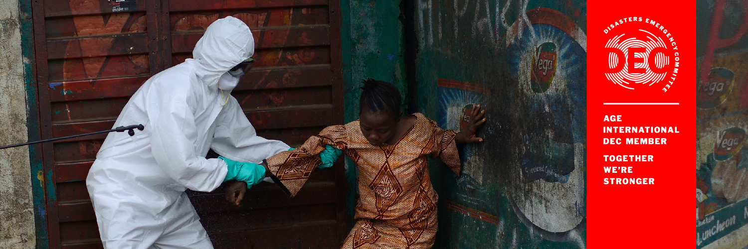 An older woman is helped out of ditch during the Ebola crisis.