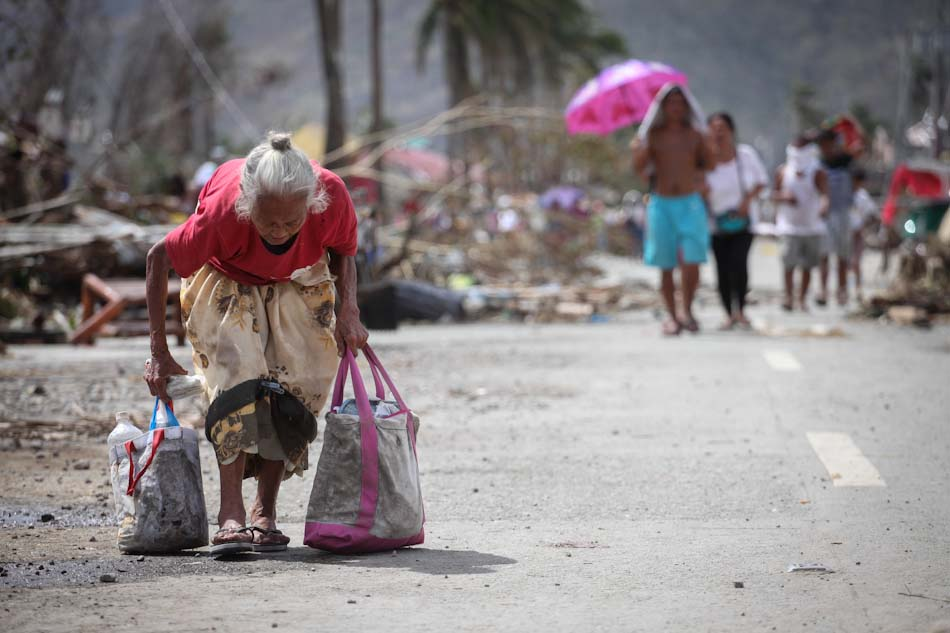 An older woman carries her possessions following the destruction of Typhoon Haiyan.