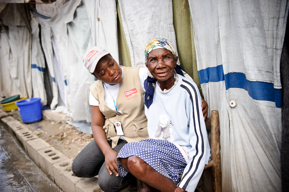 Help Age International officer comforts an older woman in Haiti.