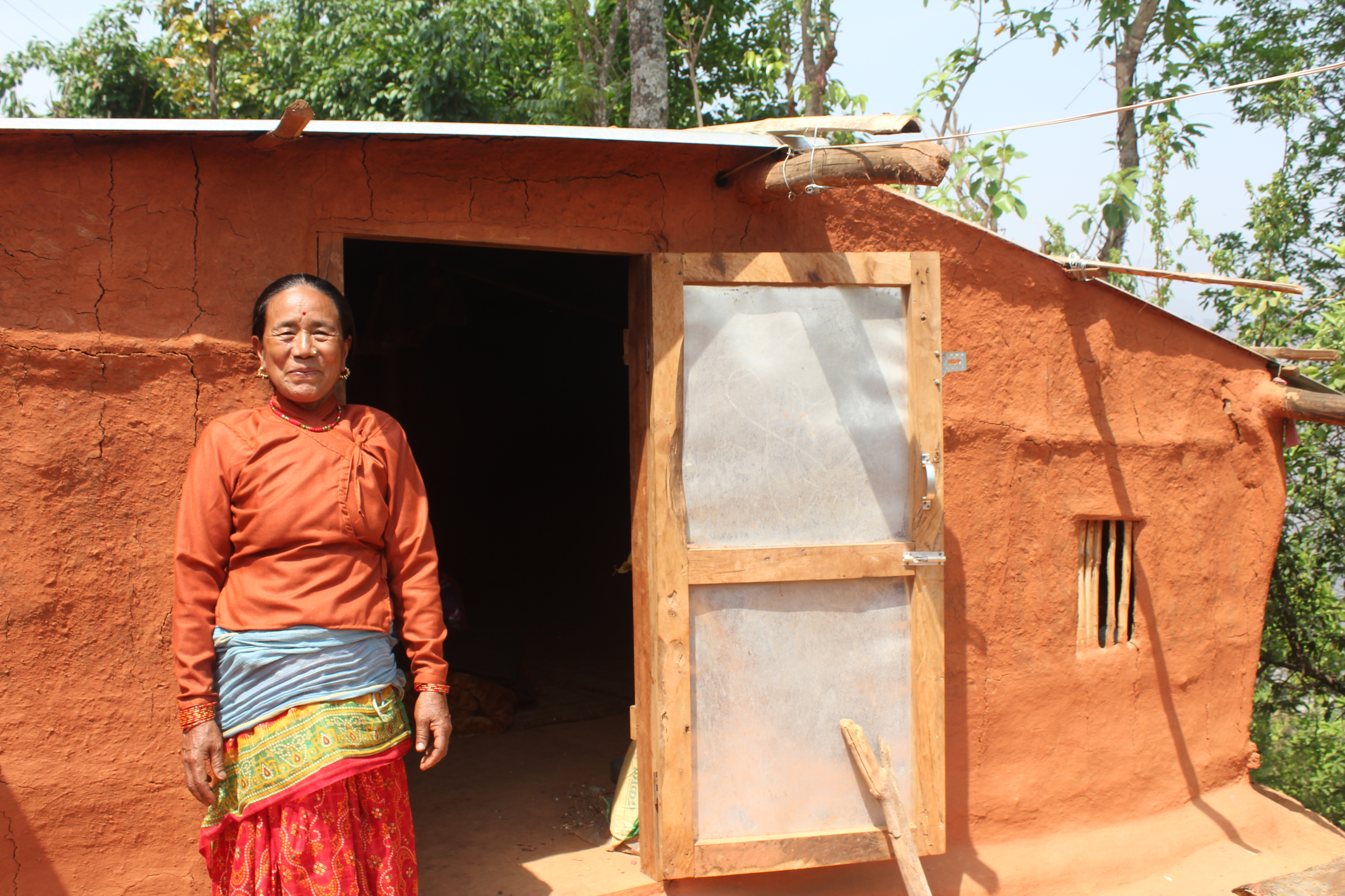 Kanchi stands outside her new house in Nepal.