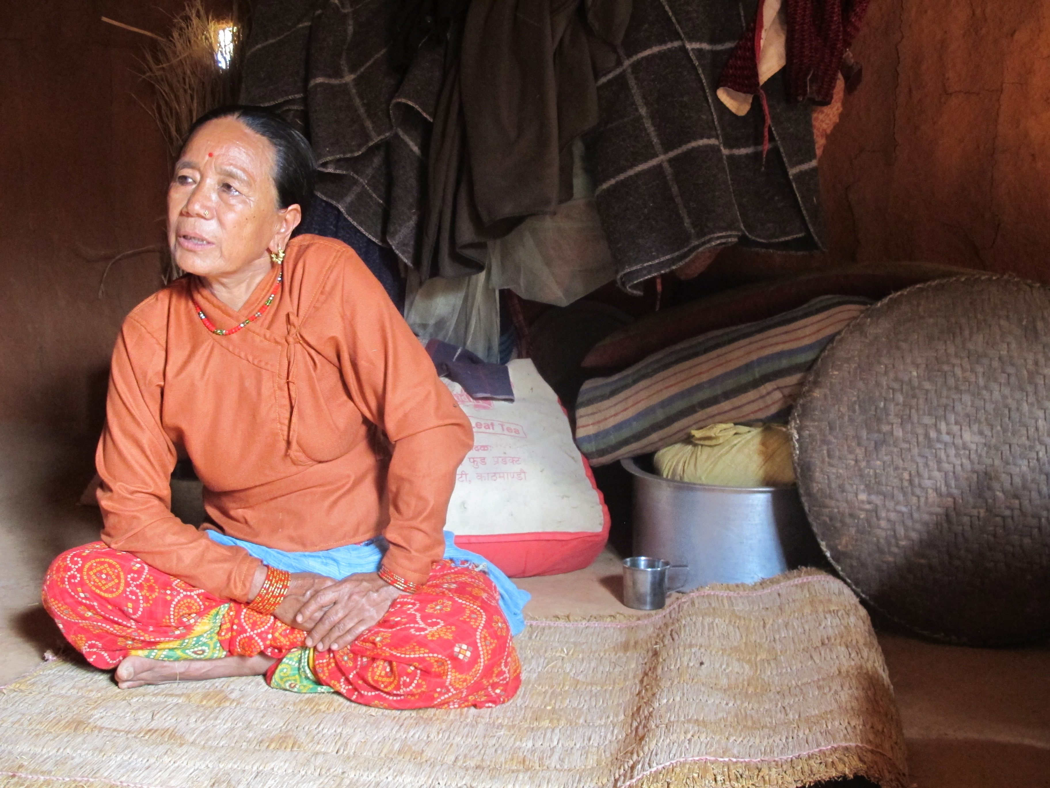 Kanchi sits on a mat in her house.