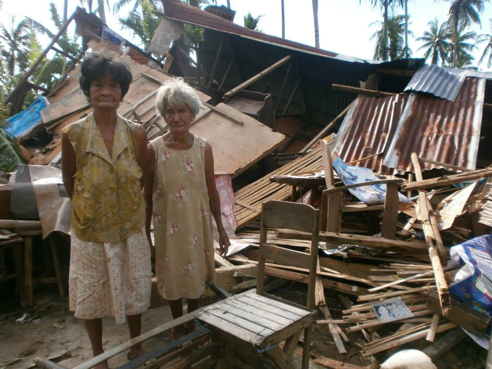 Two older women stand next to their destroyed house..