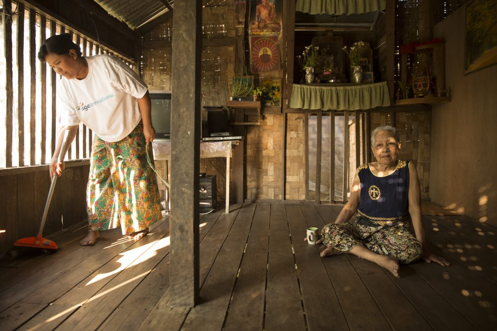 An older woman sits whilst another woman cleans in Myanmar.