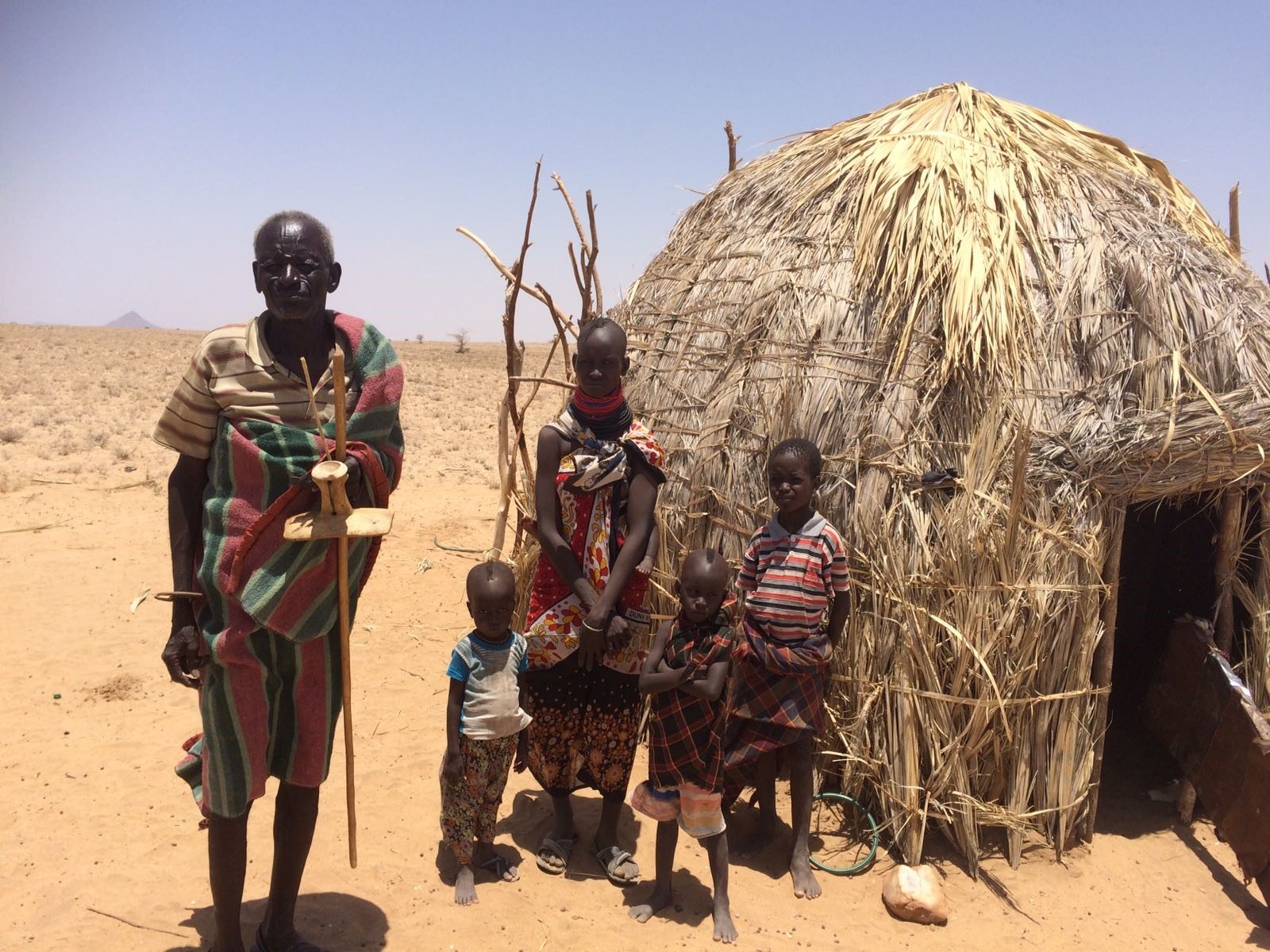 A family stands outside their house during the East Africa Drought.