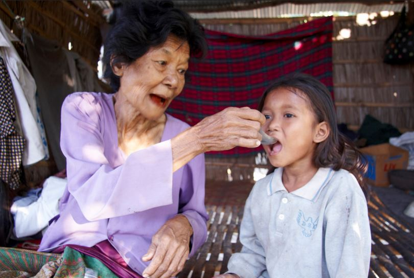 An older woman feeds her granddaughter in Cambodia.