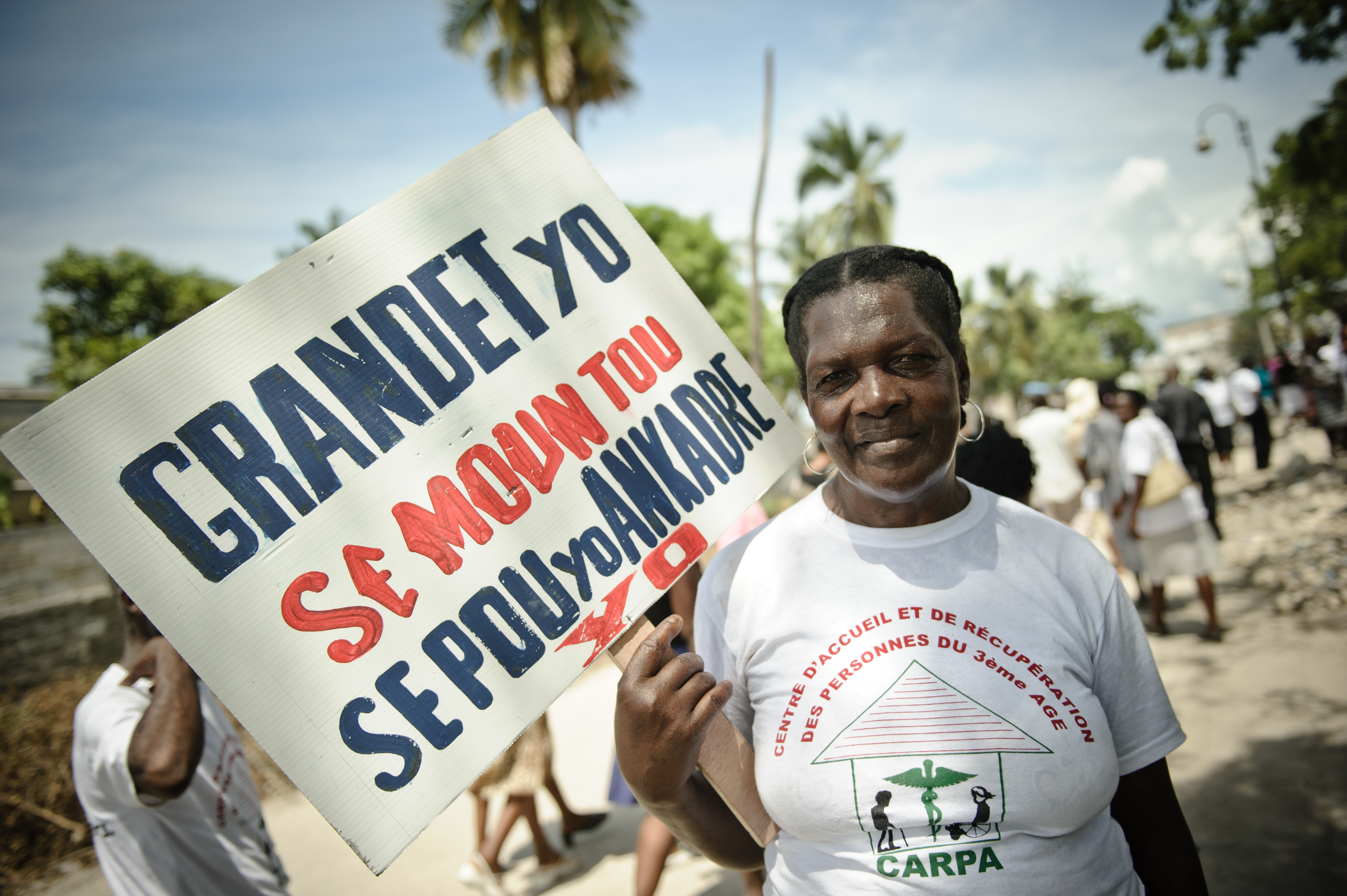An older woman marching for her rights in Haiti.