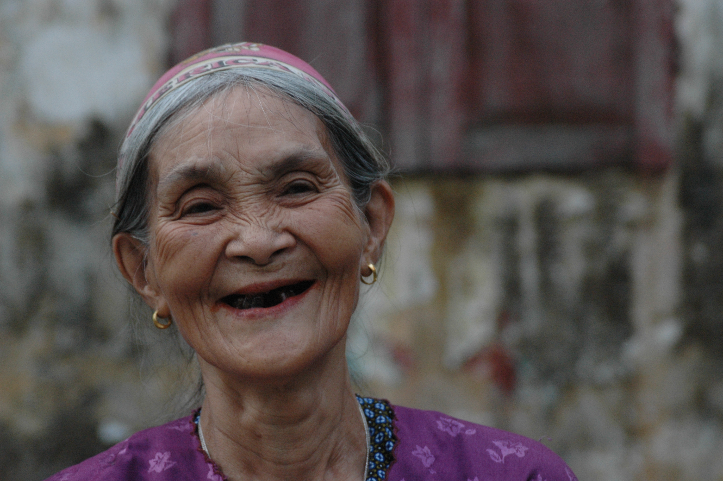 An older woman smiles widely in Myanmar.