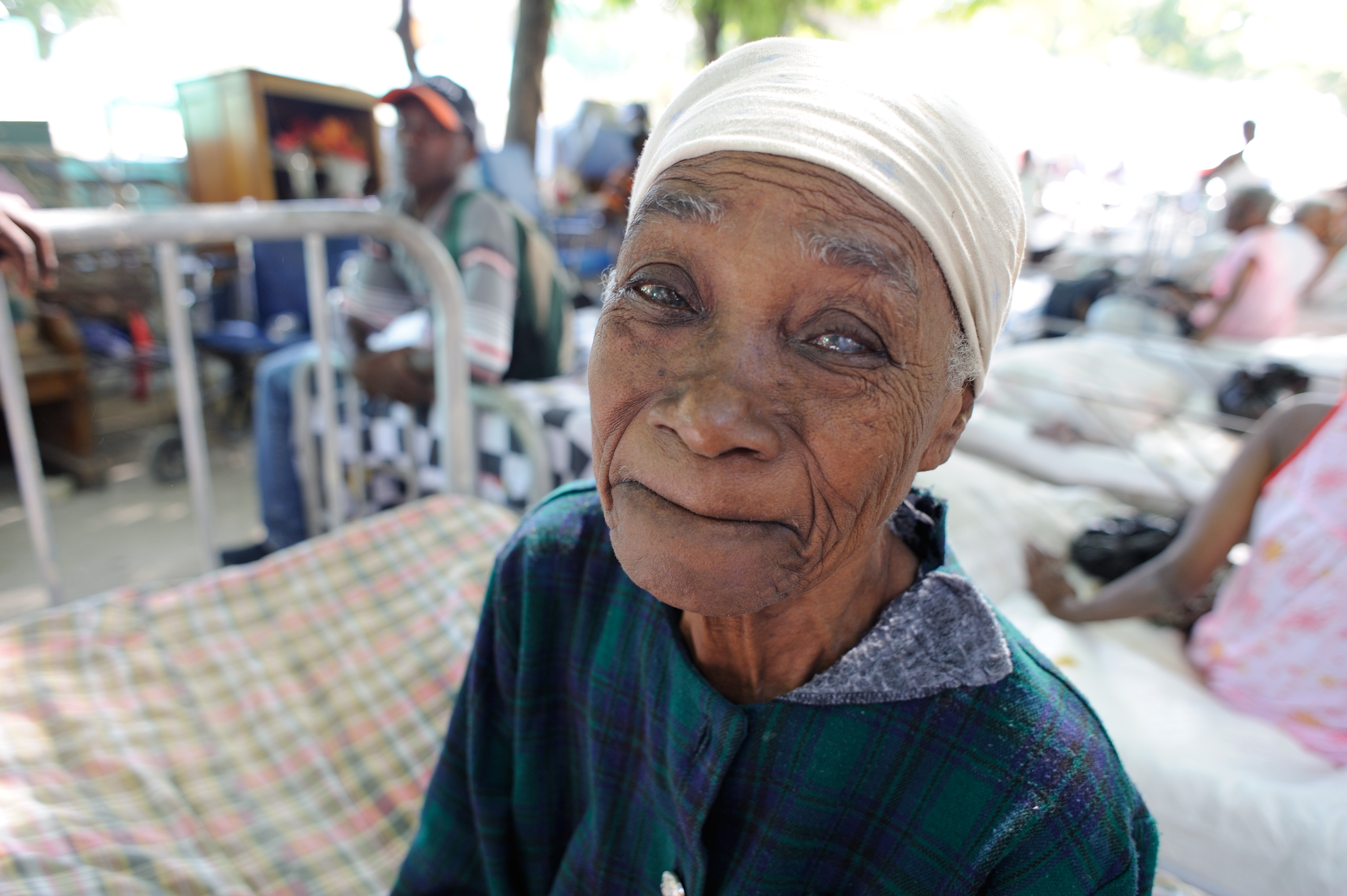 An older woman sitting on a bed in Haiti.