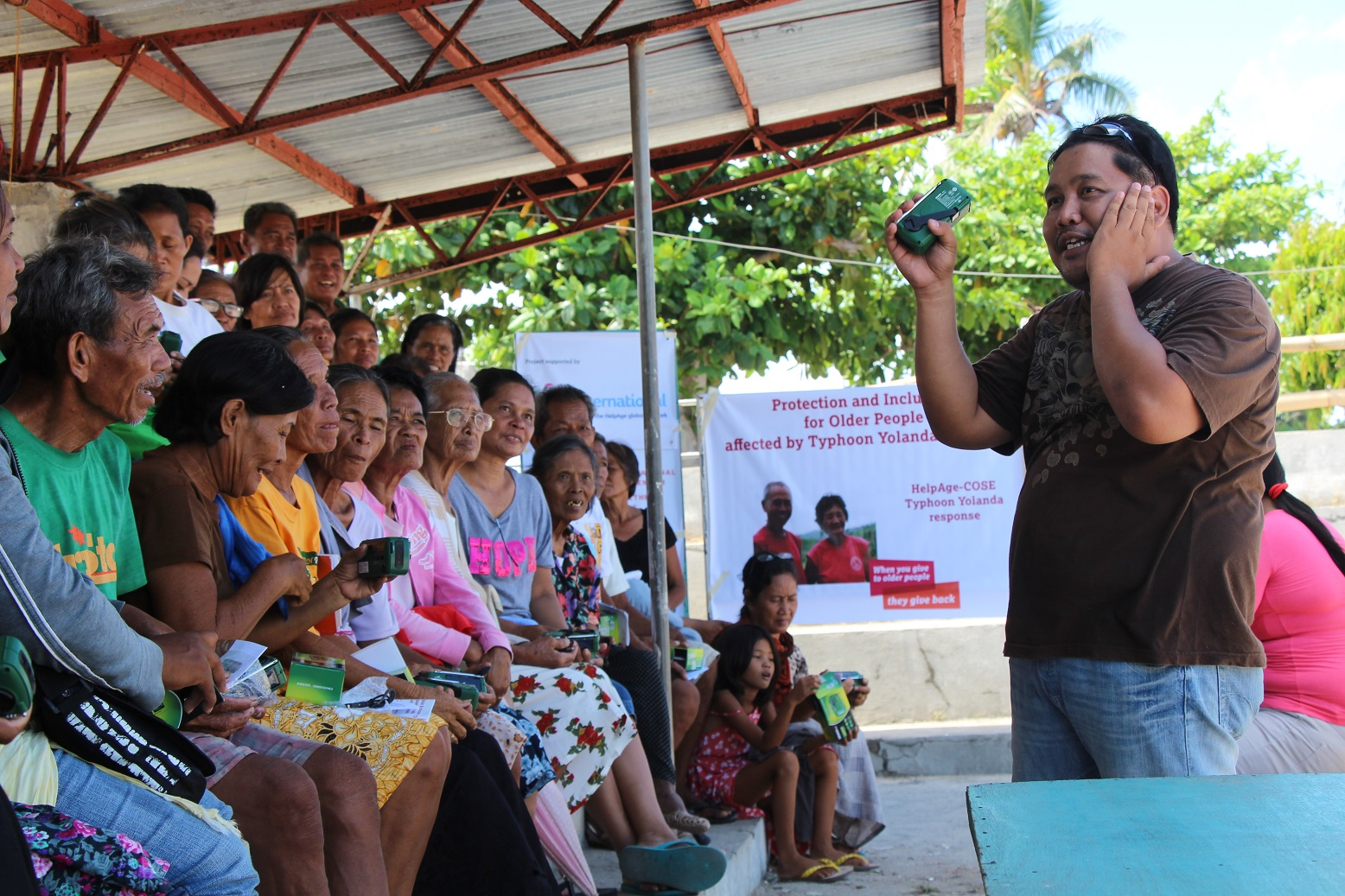 Radios are handed out to older people in the Philippines.