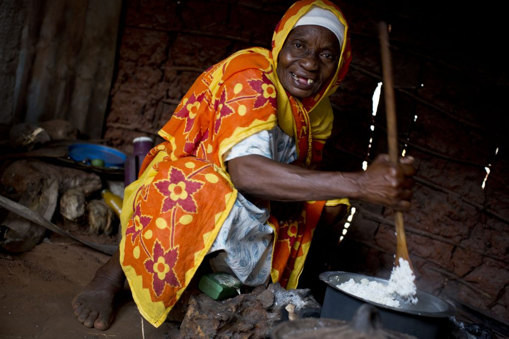 Older woman in Zanzibar bends over to cook a pot of rice.