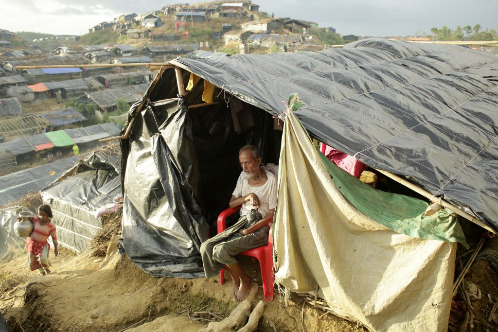 Abdur Rahim, 75, sits in the entrance to his makeshift tent, which is 60 feet up the side of a hill