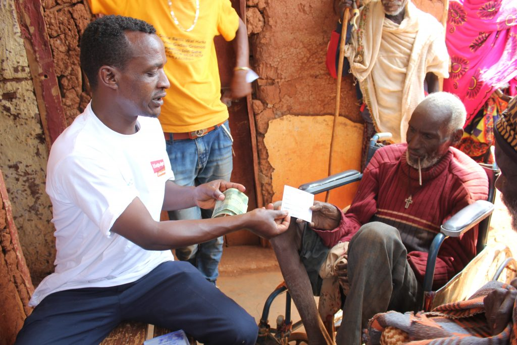 An older person in Ethiopia gets cash support from Age International's parnter