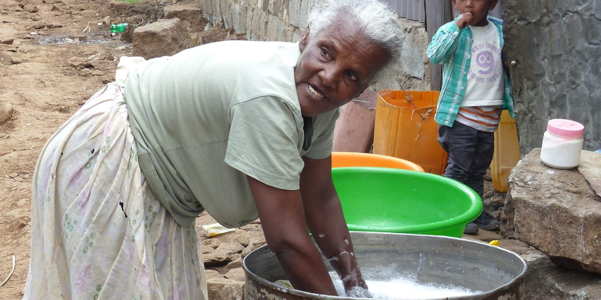 Older woman washes clothes